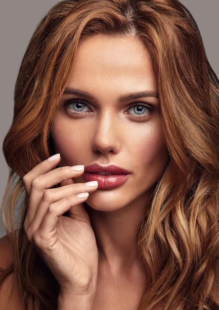 自然化粧と完璧な肌のポーズを持つ若いブロンドの女性モデルの美容ファッションの肖像画。彼女の口に触れる 無料写真