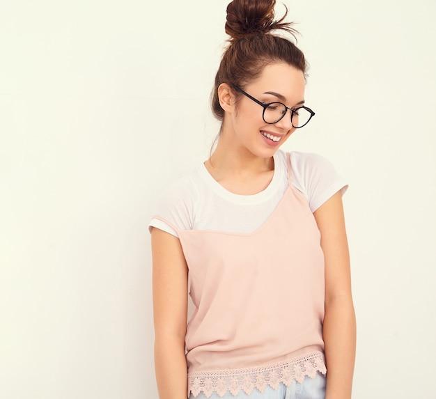Портрет молодой красивой женщины брюнетка девушка модель с обнаженной макияж в красочных летних розовый битник одежду позирует возле стены. Бесплатные Фотографии