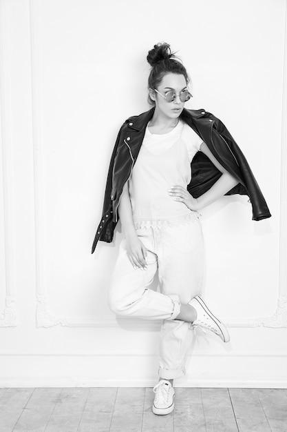 壁に近いポーズのサングラスで夏流行に敏感なバイカーレザージャケット服を着て裸化粧と若いブルネット美人少女モデルの肖像画。 無料写真