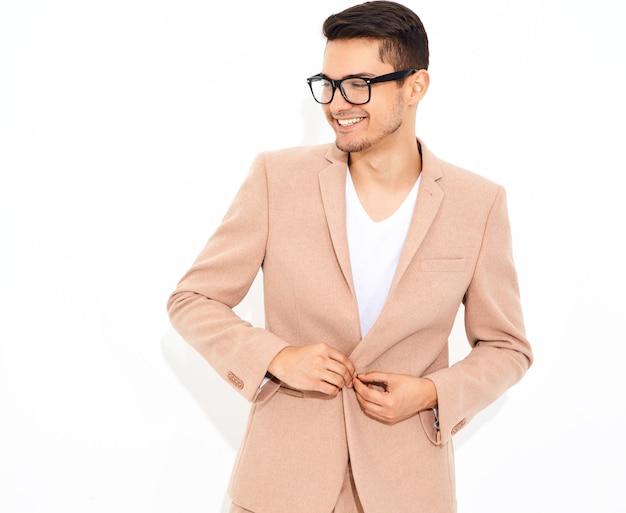 エレガントな明るいピンクのスーツのポーズに身を包んだハンサムなファッションスタイリッシュなビジネスマンモデルの肖像画。メトロセクシャル 無料写真