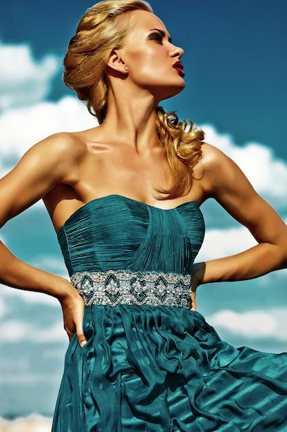 Молодая сексуальная блондинка модель в вечернем платье позирует на фоне голубого неба Бесплатные Фотографии