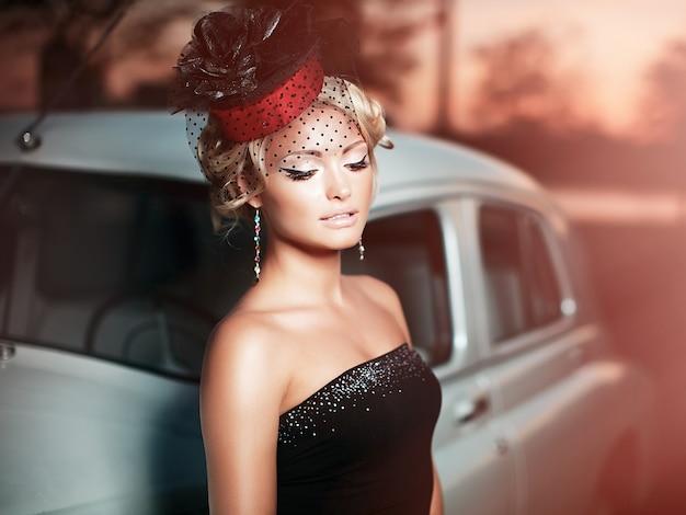 Красивая сексуальная модная блондинка модель с ярким макияжем и фигурной прической в стиле ретро, сидя в старом автомобиле Бесплатные Фотографии