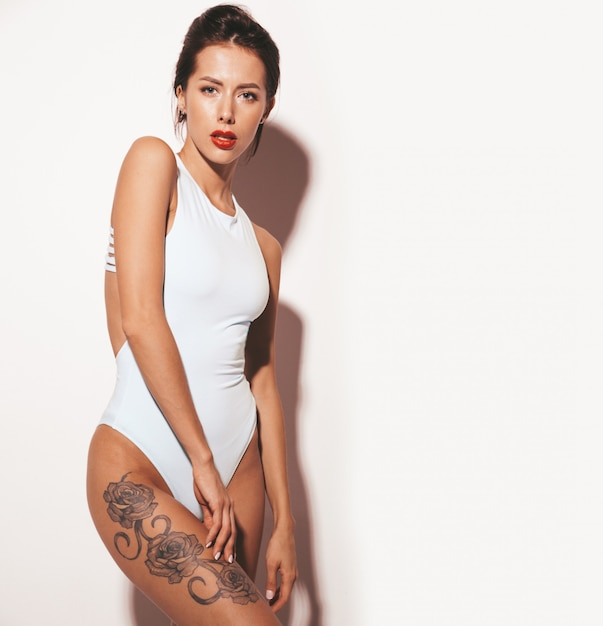 Портрет красивой сексуальной улыбающейся брюнетки. девушка, одетая в повседневные летнее голубое тело белье. модель на белом фоне Бесплатные Фотографии