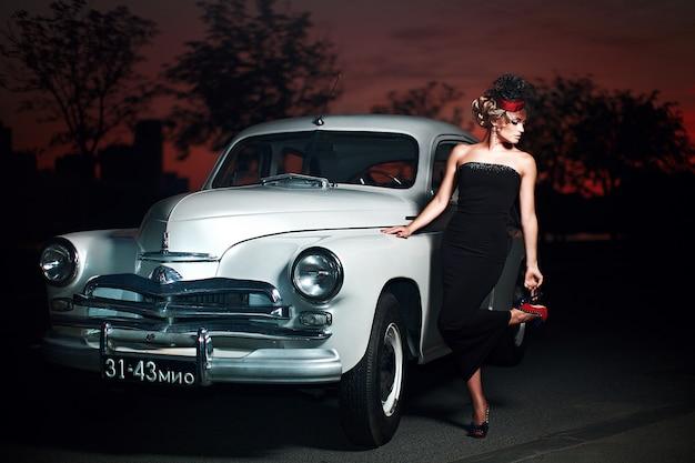 明るい化粧と古い車に座っているレトロなスタイルの巻き毛のヘアスタイルと美しいセクシーなファッションのブロンドの女の子モデル 無料写真