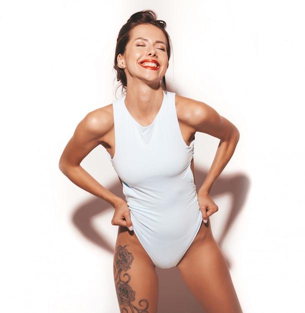 美しいセクシーな笑顔ブルネットの女性の肖像画。カジュアルな夏の青いボディランジェリーに身を包んだ女の子。白い背景で隔離のモデル 無料写真