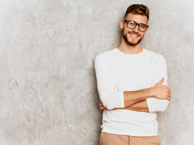 カジュアルな夏の白い服を着てハンサムな笑みを浮かべて流行に敏感なビジネスマンモデルの肖像画。 無料写真