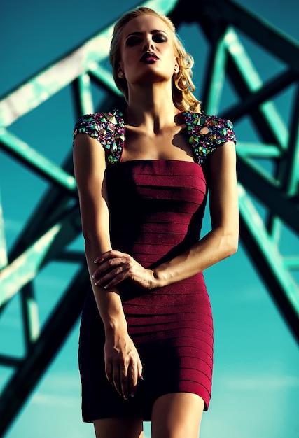 Молодая сексуальная блондинка модель в вечернем красном платье позирует на фоне голубого неба Бесплатные Фотографии