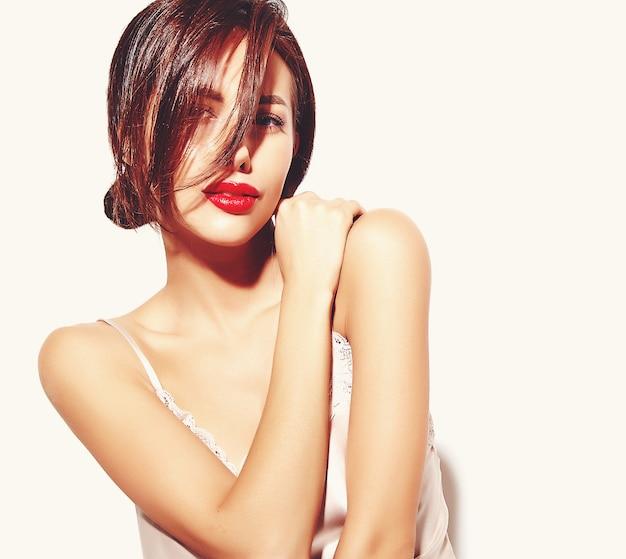 白い背景の上のパジャマランジェリーの赤い唇と美しい幸せかわいいセクシーなブルネットの女性の肖像画 無料写真