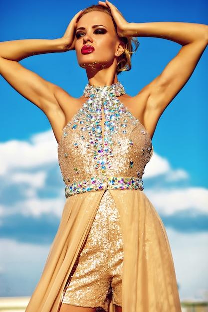 青い空を背景にポーズをとって黄色の夜のドレスで若いセクシーな金髪の女性モデル 無料写真