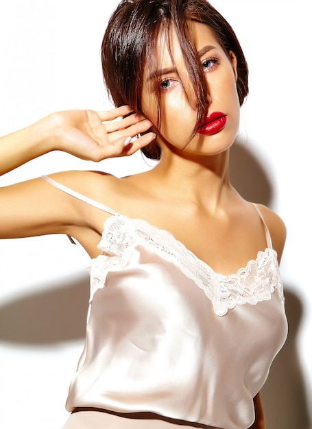 Портрет красивой счастливой милая сексуальная брюнетка женщина с красными губами в пижаме белье на белом фоне Бесплатные Фотографии