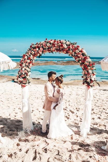 青い空と海の背後にあるビーチで結婚式の熱帯のアーチに近いポーズ新郎新婦の肖像画。結婚式のカップル 無料写真