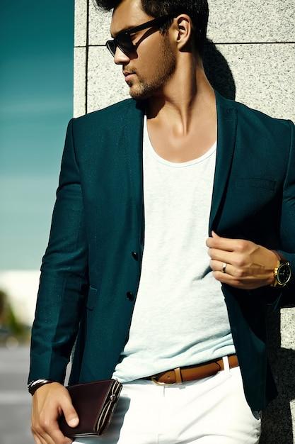 通りにサングラスでカジュアルな布スーツの若いセクシーな実業家ハンサムなモデル男のファッションポートレート 無料写真