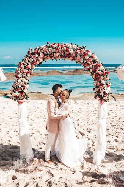 Портрет жениха и невеста представляя около арки свадьбы тропической на пляже за голубым небом и морем. свадебная пара Бесплатные Фотографии