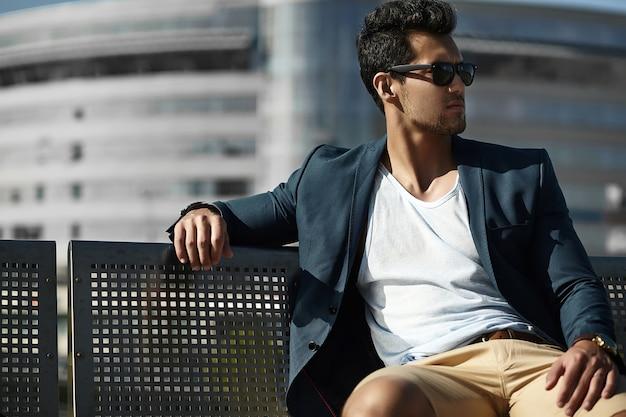 Фасонируйте портрет молодого сексуального бизнесмена красивого модельного человека в вскользь костюме ткани в солнечных очках сидя на стенде на улице Бесплатные Фотографии