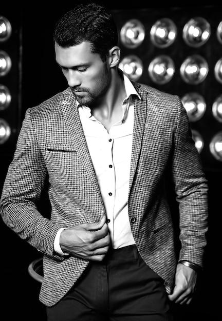 Портрет сексуального красивого модного мужчины модели человека, одетого в элегантный костюм на черном фоне студии огни Бесплатные Фотографии