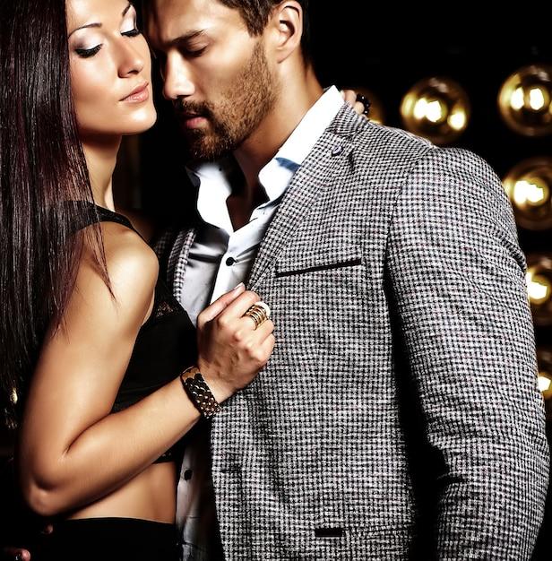 Фасонируйте фото красивого элегантного человека в костюме при красивая сексуальная женщина представляя на черной предпосылке светов студии Бесплатные Фотографии