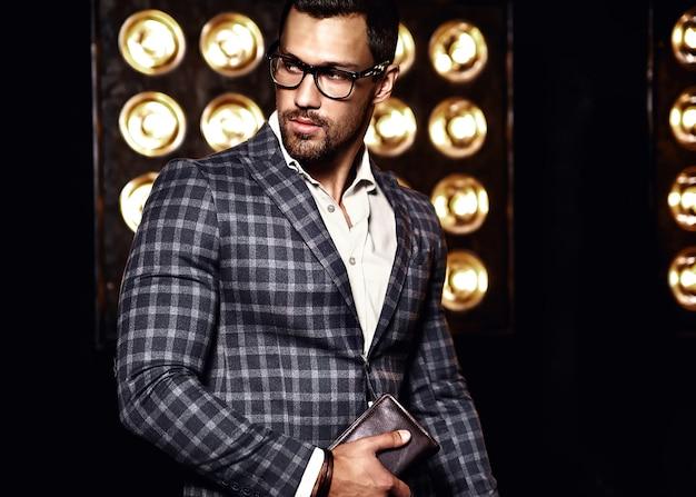 Портрет сексуального красивого модного мужчины модели человека, одетого в элегантный костюм на черном фоне студии огни в очках Бесплатные Фотографии