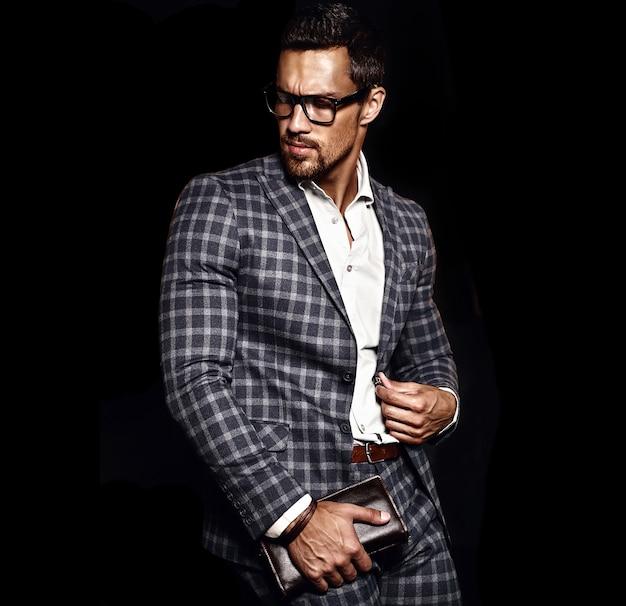 Портрет сексуального красивого модного мужчины модельного человека, одетого в элегантный костюм на черном фоне Бесплатные Фотографии
