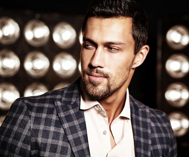 黒のスタジオライトの背景にエレガントなスーツに身を包んだセクシーなハンサムなファッション男性モデル男の肖像 無料写真