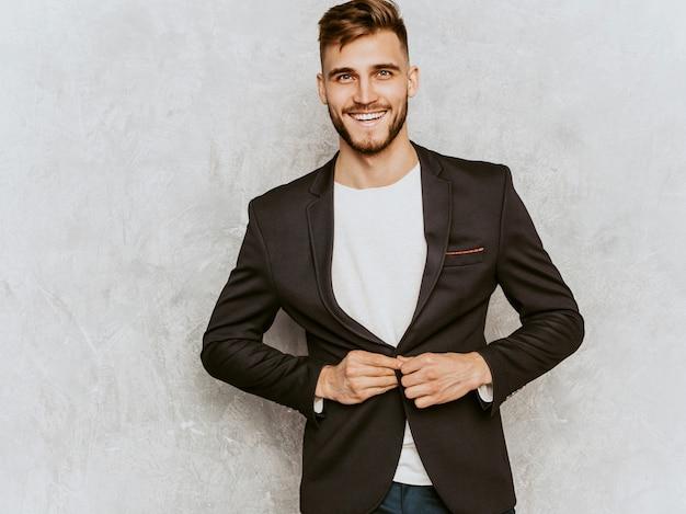カジュアルな黒のスーツを着ているハンサムな笑顔ヒップスター実業家モデルの肖像画。 無料写真