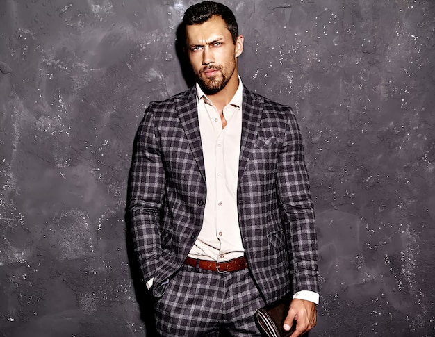 灰色の壁に近いポーズのエレガントなスーツに身を包んだセクシーなハンサムなファッションの男性モデルの男の肖像 無料写真