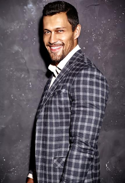 Портрет сексуальный красивый модный мужчина модель мужчина одет в элегантный костюм позирует возле серой стены Бесплатные Фотографии