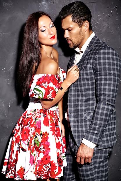 灰色の壁に近いポーズ美しいセクシーな女性とスーツを着たハンサムなエレガントな男のファッション写真 無料写真