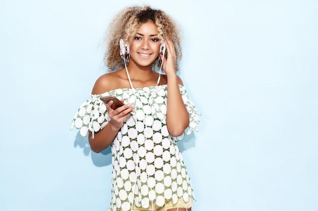 Женщина улыбается и слушает музыку в наушниках Бесплатные Фотографии