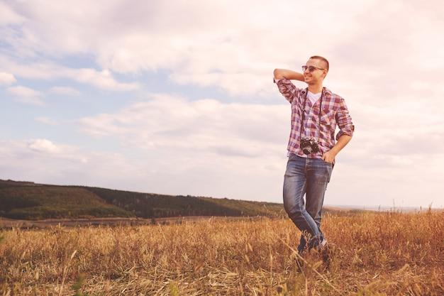 レトロな写真カメラ屋外ヒップスターライフスタイルと若い男 無料写真