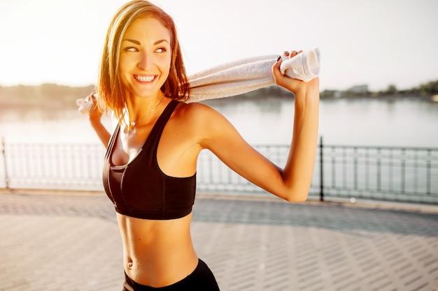 スポーツ少女の肖像画。都市公園でジョギングの準備をしている美しい若いスポーツフィットネスモデル。 無料写真