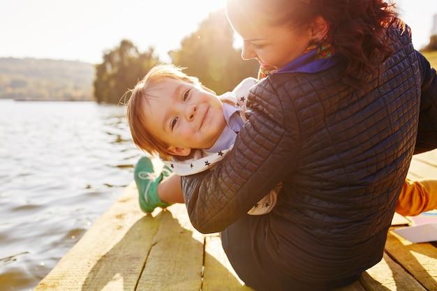 Мама и сын веселятся на берегу озера Бесплатные Фотографии