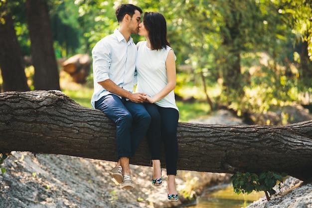 Красивая беременная пара расслабляющий снаружи в лесу Бесплатные Фотографии