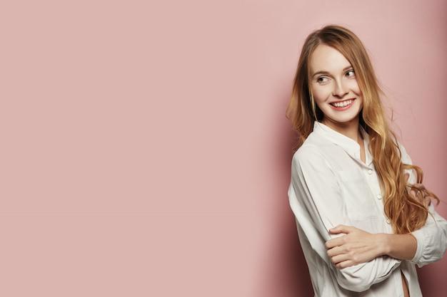 ピンクの背景にポーズかなり若い女性 無料写真