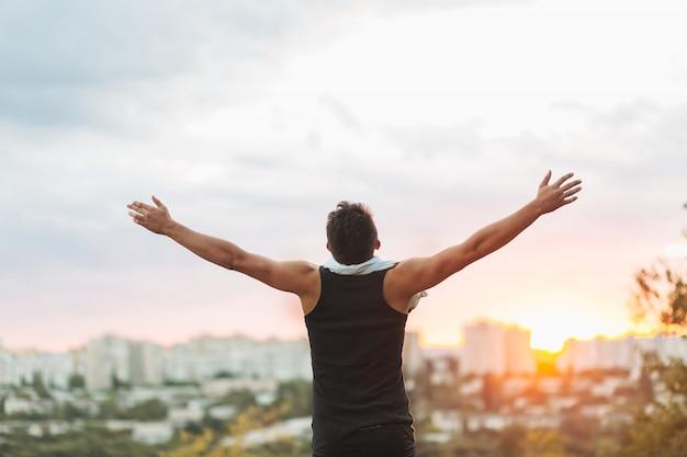 トレーニング後の夕焼け空に手を上げる若い男 無料写真