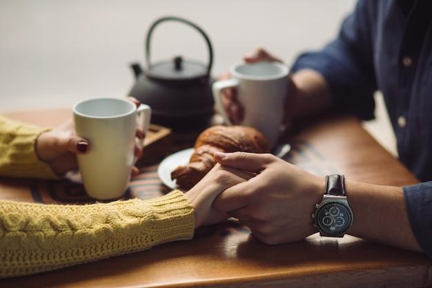 コーヒーを飲むことを愛するカップル。手がクローズアップ 無料写真