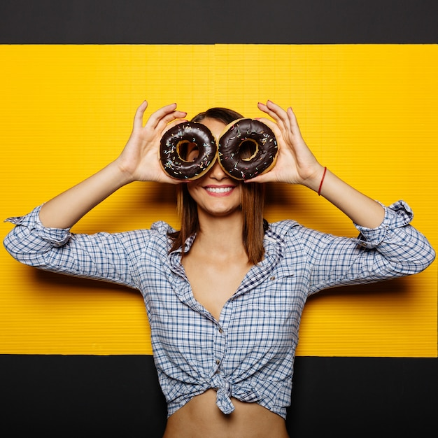 チョコレートのアイシングでドーナツを保持している女の子 無料写真