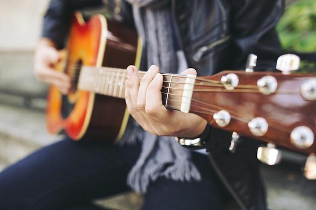 Молодой привлекательный уличный артист со своей гитарой Бесплатные Фотографии