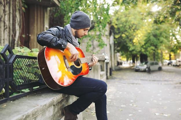Молодой музыкант с гитарой в городе Бесплатные Фотографии