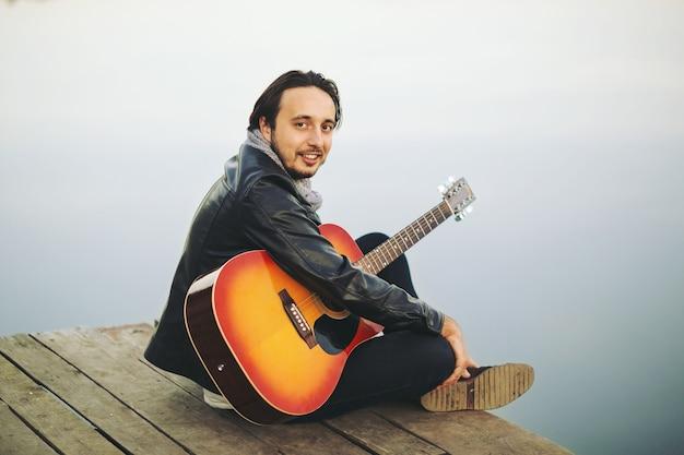 湖でギターを弾く若い男 無料写真