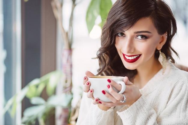 Молодая девушка пьет кофе в модном кафе Бесплатные Фотографии