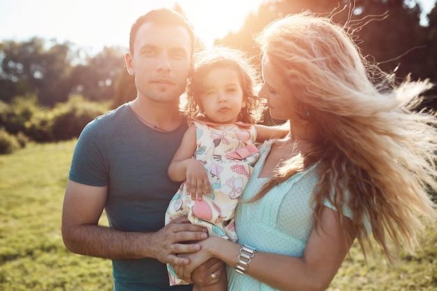 緑の自然の中で外で一緒に時間を過ごす幸せな若い家族。 無料写真