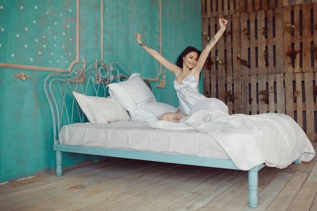 目を覚ます後ベッドでストレッチの女性 無料写真
