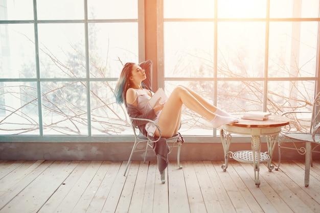 Книга чтения молодой женщины сидя около окна Бесплатные Фотографии