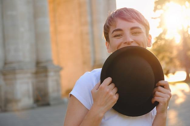美しい女性の目を示す帽子の後ろに顔を隠す 無料写真
