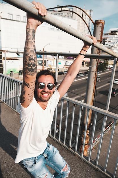 都市に出かけるサングラスを持つ魅力的な男 無料写真
