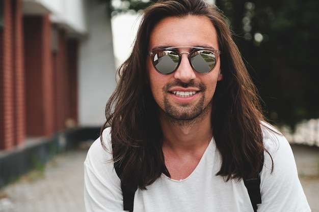 笑みを浮かべて都市のシーンにサングラスをかけた肖像画魅力的な男 無料写真