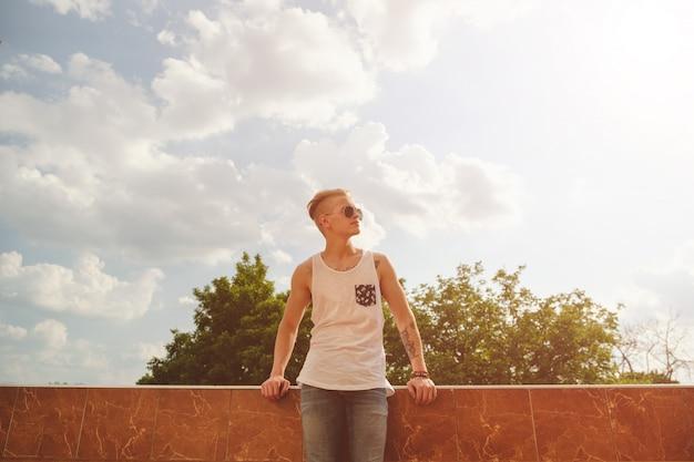 若い男がリラックスして、ブイに立っている間晴れた日を楽しんでいます 無料写真