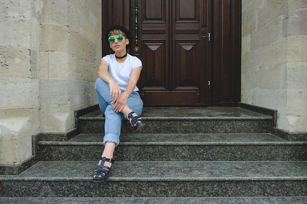 階段の上に座ってポーズ美しい若い流行に敏感な女性 無料写真