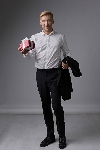 Стильный бизнесмен держит подарочную коробку Бесплатные Фотографии
