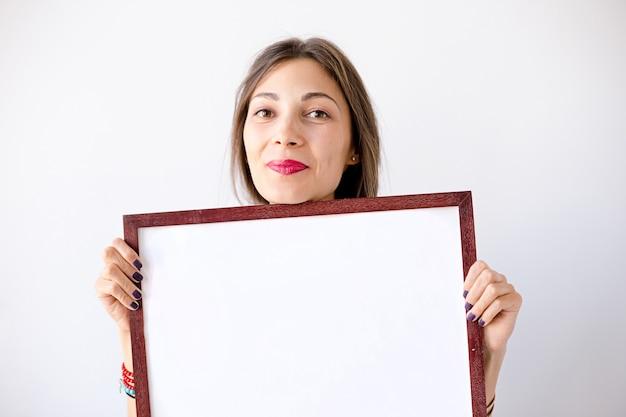Макро улыбается девушка с пустым белым плакатом или плакатом Бесплатные Фотографии